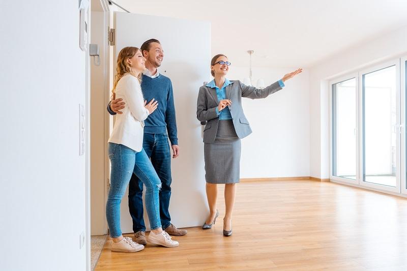 para młodych ludzi oraz agent nieruchomości stoją w pustym mieszkaniu